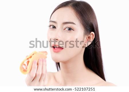 Young beautiful woman eating sausage or hotdog. Natural makeup, isolated over white background.