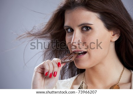 Young beautiful woman eating some chocolate - stock photo