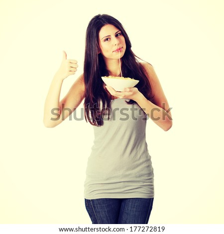Young beautiful woman eating spaghetti, isolated on white background - stock photo