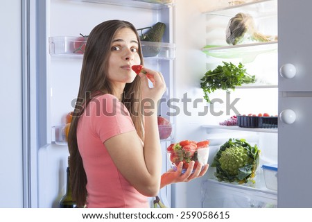 young beautiful woman eating strawberries from the fridge. Healthy Eating Concept. - stock photo