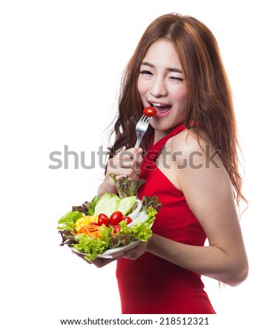Young beautiful woman eating vegetable salad on white background