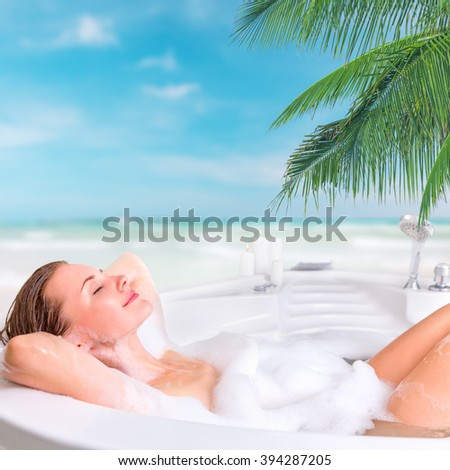 Young beautiful woman enjoying bath at the resort in outdoor whirlpool bathtub - stock photo