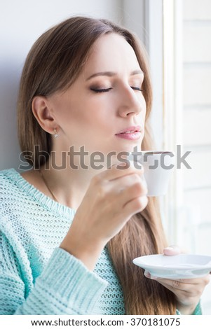 Young beautiful woman enjoying cup of espresso sitting near the window. - stock photo