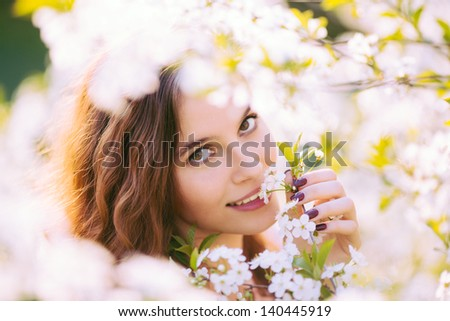 Young beautiful woman enjoying smell of blooming tree on a sunny day (selective DOF) - stock photo