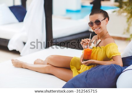 young beautiful woman Enjoying summer vacation. Beautiful young woman in yellow dress holding glass with cocktail while relaxing in deck chair near the pool. beautiful, sexy woman drinking cocktail - stock photo