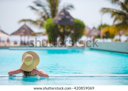 Young beautiful woman enjoying summer vacation in luxury swimming pool - stock photo