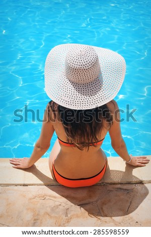 Young beautiful woman enjoying the sun and sitting on edge of the pool. - stock photo