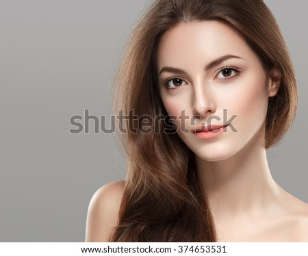 Young beautiful woman face portrait with healthy skin on gray background