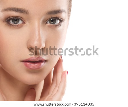 Young beautiful woman face portrait with healthy skin with fingers on cheek - stock photo