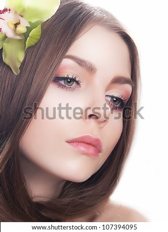 Young beautiful woman face with fresh orchid flower close-up portrait. Clean healthy skin - stock photo