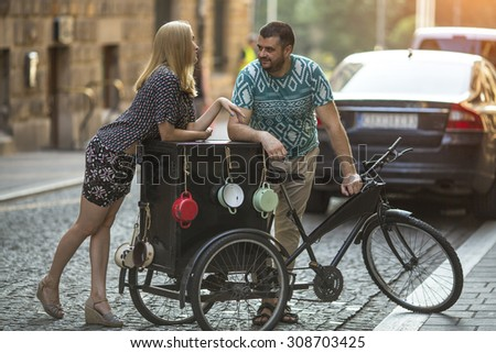 Young beautiful woman flirts with a man near vintage bike on the street. - stock photo