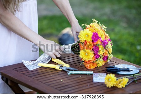 Young beautiful woman florist. The girl in the Park draws a bouquet. Outdoor - stock photo