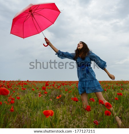 Young beautiful woman flying with wind holding red umbrella from a poppy field, summer outdoor. - stock photo