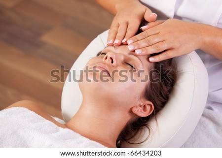 Young beautiful woman getting facial massage. Spa studio shot - stock photo
