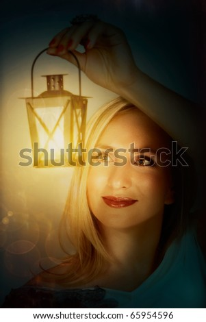young beautiful woman hanging a lantern with bright light - stock photo