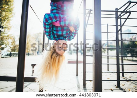 Young beautiful woman hanging upside down on horizontal bar at calisthenics park, looking at the camera arms crossed on chest. Natural sun flare is visible on picture.