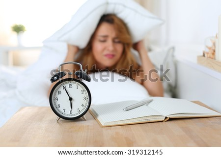 Young beautiful woman hates waking up early in the morning. Sleepy girl looking at alarm clock and trying to hide under the pillow - stock photo