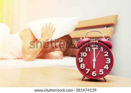 Young beautiful woman hates waking up early in the morning. Sleepy girl looking at alarm clock and trying to hide under the pillow in the morning - stock photo