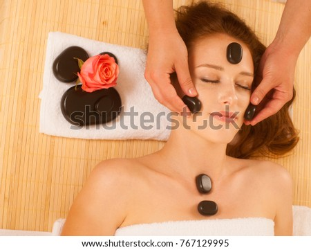 young beautiful woman having facial massage with mineral stone