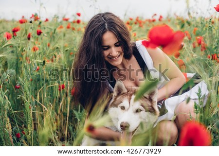young beautiful woman having fun with siberian husky dog in poppy field - stock photo