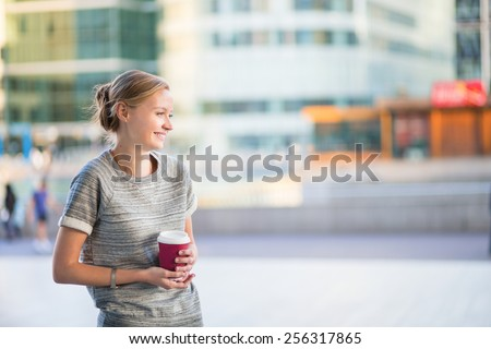 Young beautiful woman having her coffee break outside of the office or university  - stock photo