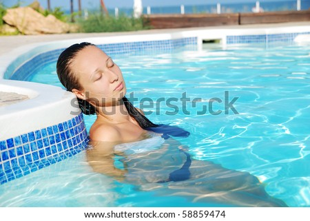 Young beautiful woman having rest in swimming-pool