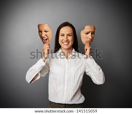 young beautiful woman hiding her good mood under masks - stock photo