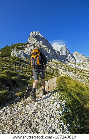 Young beautiful woman hiking in mountains with walking sticks  - stock photo