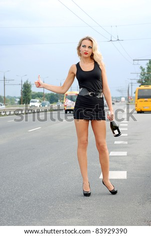 Young beautiful woman hitching a lift at the road