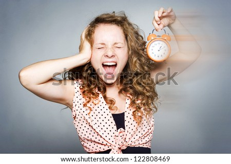 Young beautiful woman holding a clock - stock photo