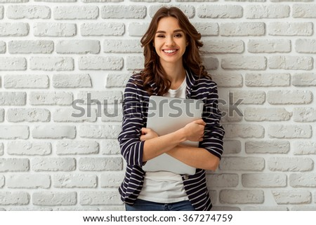 Young beautiful woman holding a laptop, dressed in a striped jacket and blue trousers on background brick wall. Close-up - stock photo