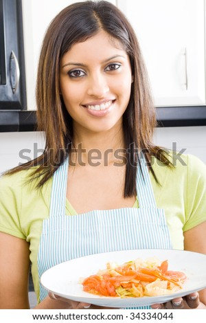 young beautiful woman holding a plate of cooked food - stock photo