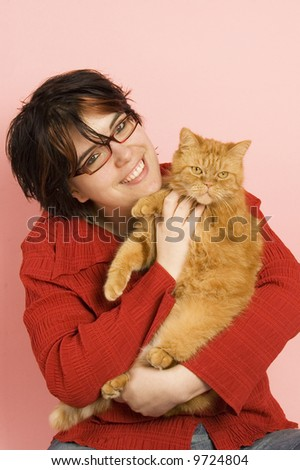 young beautiful woman holding a red domestic cat - stock photo