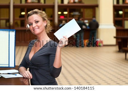 Young beautiful woman holding a white empty letter, sitting at the table and smiling
