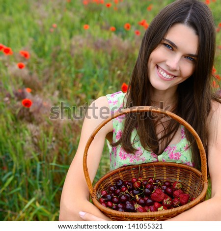 Young beautiful woman holding basket with cherry and strawberry on a poppy field, summer nature outdoor. - stock photo