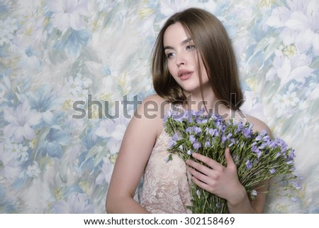 Young beautiful woman holding bunch of wild flowers. Studio shot of attractive girl looking at camera over white background. Toned. - stock photo