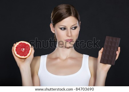 Young beautiful woman holding chocolate and grapefruit in her hands making decision