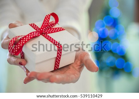 Young beautiful woman holding Chrismtas present in her hands in front of a beautifully decorated Christmas tree.