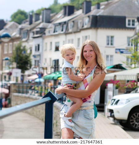 Young beautiful woman holding her little daughter, adorable blonde toddler girl in casual outfit, outdoors in urban environment - mother and child concept - stock photo