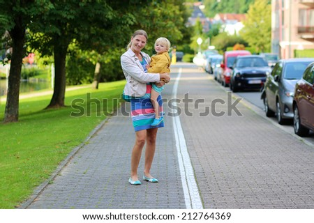 Young beautiful woman holding her little daughter, adorable blonde toddler girl in colorful yellow coat, outdoors in urban environment - mother and child concept - stock photo