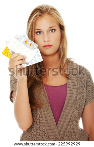 Young beautiful woman holding pills - stock photo