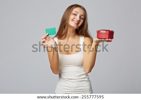 Young beautiful woman holding small red box and credit card, on gray background - stock photo