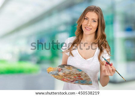 Young beautiful woman holing paintbrush and palette