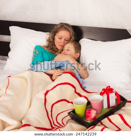 Young beautiful woman hugging her son in bed