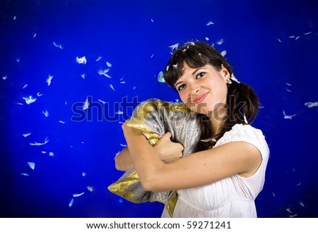 Young beautiful woman hugs the pillow on a blue background with feathers - stock photo