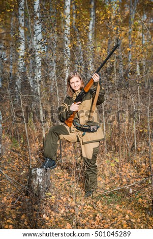 Young beautiful woman hunter with a shotgun in the forest