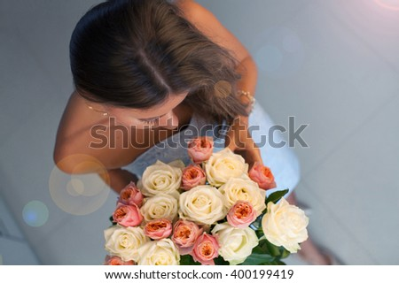 Young beautiful woman in a blue dress posing with a bouquet of roses. Holidays and celebration concept. (focus on nose) - stock photo