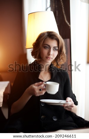 Young beautiful woman in a cafe. Modern trendy blondy girl in the restaurant. - stock photo