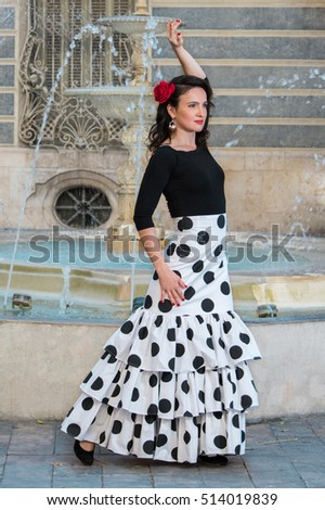 Young beautiful woman in a flamenco costume. Fountain on the background.