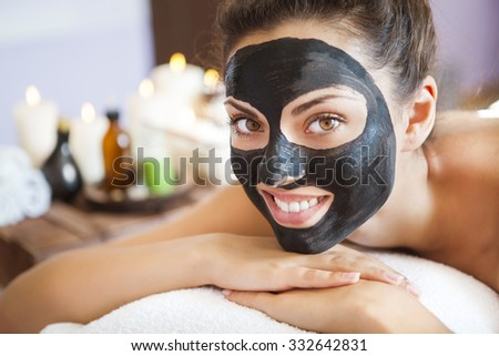Young beautiful woman in a mask for the face of the therapeutic black mud. Spa treatment - stock photo
